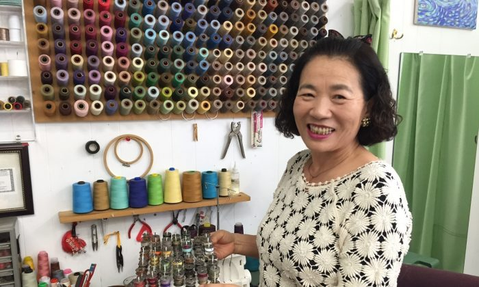 In this photo taken on April 2, 2016, tailor Grace Myung Lee, 61, smiles holding up a tray of small spools of sewing machine thread in her dry cleaning and alterations shop Grace Cleaners in Pasadena, Calif., that she co-owns with her husband Sung Jae Lee. (Solvej Schou via AP)