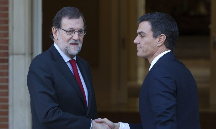 Spain's acting Prime Minister Mariano Rajoy (L) shakes hands with main Socialist opposition leader Pedro Sanchez before a meeting at the Moncloa Palace in Madrid, Spain, on Dec. 23, 2016. (AP Photo/Paul White)