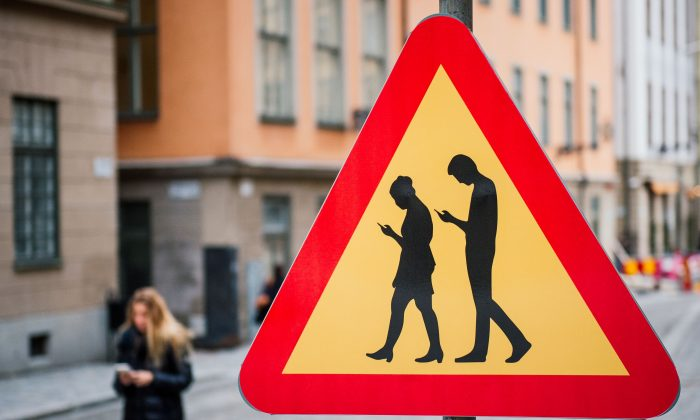 A road sign Warning Against pedestrians focusing on their smartphones, near the old town in Stockholm on Feb. 2, 2016. (Jonathan Nackstrand/AFP/Getty Images)
