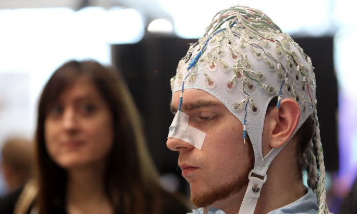 A young woman watches a man, wearing an EEG brain scanning apparatus on his head, play a pinball game solely through willing the paddles to react with his brain at the Berlin Brain Computer Interface research consortium stand at the CeBIT Technology Fair in Hannover, Germany, on March 2, 2010. (Sean Gallup/Getty Images)