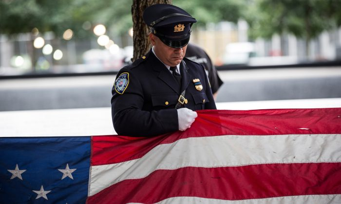 A Port Authority Police officer prepares to present an American flag that survived the terrorist attacks of Sept. 11, 2001, during an anniversary ceremony in New York City on Sept. 11, 2015. (Andrew Burton/Getty Images)