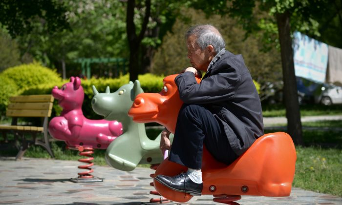 An elderly man sits on a hobby horse at a residential area in Beijing on May 4, 2015.  (WANG ZHAO/AFP/Getty Images)