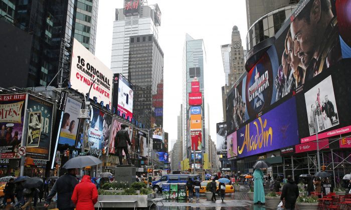 """Pedestrians walk through Times Square, Sunday, May 1, 2016, in New York, where Clear Channel Outdoor Americas operates some billboards. New York Sen. Charles Schumer is calling for a federal investigation into the advertising company's latest effort to target billboard ads to specific consumers with its so-called RADAR program which he calls """"spying billboards,"""" and warns that the service may violate privacy rights by tracking people's cell phone data. (AP Photo/Kathy Willens)"""