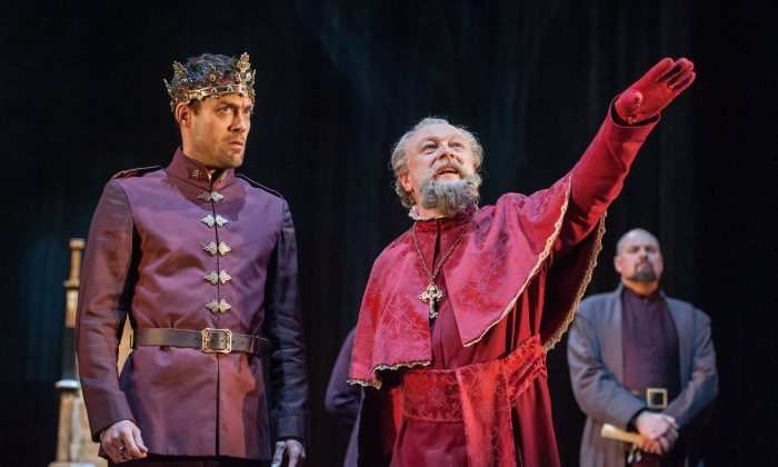 """Henry V (Alex Hassell) with the Archbishop of Canterbury (Jim Hooper) in the last in the cycle of king plays at the Brooklyn Academy of Music, """"Henry V."""" (Stephanie Berger)"""