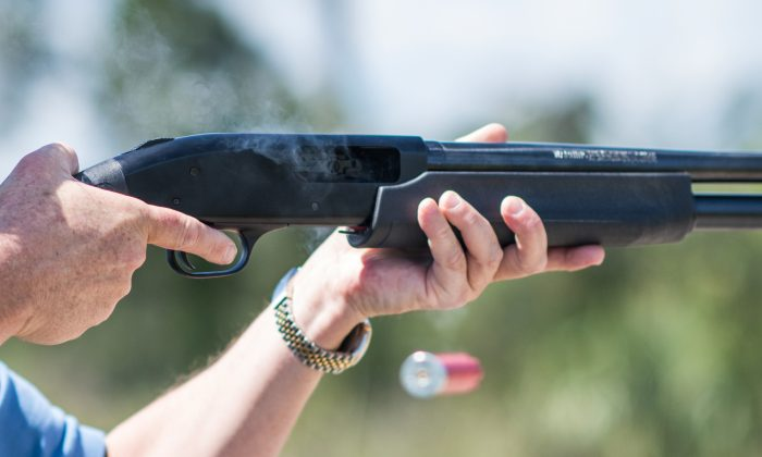 """Jonathan Mossberg, whose iGun Technology Corp. is working to develop a """"smart gun,"""" poses with the firearm in Daytona Beach, Fla., on April 7, 2016. The firearm uses a ring to send a signal to prevent anyone but an authorized user from firing the weapon. (AP Photo/Lisa Marie Pane)"""