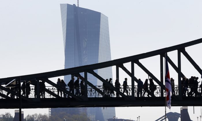 People walk over a bridge near the European Central Bank (background) in Frankfurt, Germany, on May 2, 2016. (Michael Probst/FILE PHOTO/AP)
