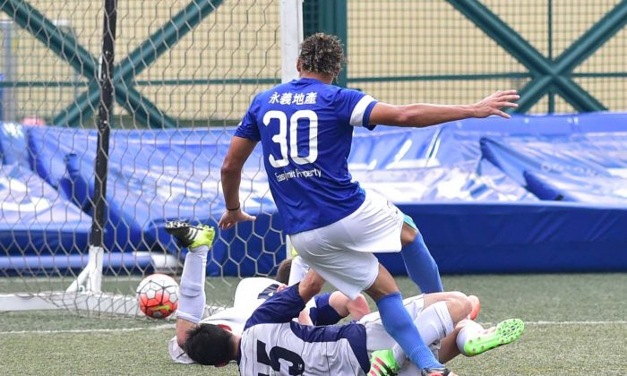 After slipping the ball past a charging Lucky Mile goalie, Beto Doc Santos, Jose Wellington of Easyknit Property, side foots the ball into the net while under pressure from two Lucky Mile defenders, increasing the lead of Easyknit Property to 4-2, the final score, in the HKFA First division match at Sports Road on Sunday May 1, 2016. (Bill Cox/Epoch Times)