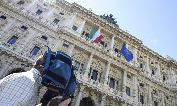 A cameraman makes a video recording in front of the Court of Cassation building, where the supreme court is set to decide whether to confirm a one-year prison sentence and a five-year ban from politics in a long-running tax fraud case involving  former Italian Prime Minister Silvio Berlusconi's media business interests, on July 30 2013 in central Rome. The final appeal hearing began on Tuesday but one of Berlusconi's lawyers told reporters that the verdict may come only on Wednesday or Thursday. AFP PHOTO / ANDREAS SOLARO        (Photo credit should read ANDREAS SOLARO/AFP/Getty Images)