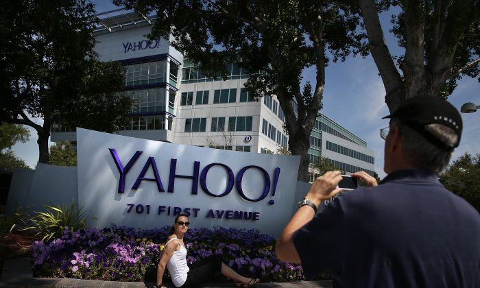People take pictures in front of a sign that posted in outside of the Yahoo! headquarters in Sunnyvale, Calif., on May 23, 2014. (Justin Sullivan/Getty Images)
