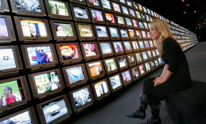 Elizabeth Muling inspects a wall of some 750 television screens at the opening of TV50, an exhibition celebrating 50 years of television broadcasting, in Melbourne, Australia, on June 21, 2006. (William West/AFP/Getty Images)