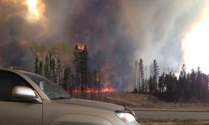 Smoke fills the air and trees burn in Fort McMurray on May 3, 2016. (The Canadian Press/Kitty Cochrane)