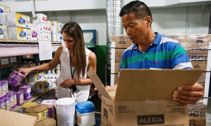 Social worker Danielle Holm, left, and Walter Dong of the Edmonton Food Bank, right, pack care packages for evacuees of the wildfires in and around Fort McMurray at the Edmonton Food Bank in Edmonton Alta, on Wednesday, May 4, 2016. THE CANADIAN PRESS/Codie McLachlan
