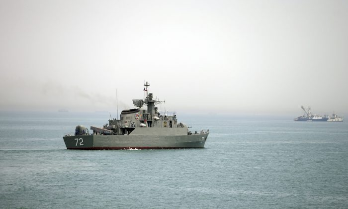"""FILE - In this Tuesday, April 7, 2015, file photo released by the semi-official Fars News Agency, Iranian warship Alborz, foreground, prepares before leaving Iran's waters, at the Strait of Hormuz.  The deputy commander of Iran's powerful Revolutionary Guard said Iranian forces will close the strategic Strait of Hormuz to the United States and its allies if they """"threaten"""" the Islamic Republic, Iranian state media reported on Wednesday, April 4, 2016. (AP Photo/Fars News Agency, Mahdi Marizad)"""