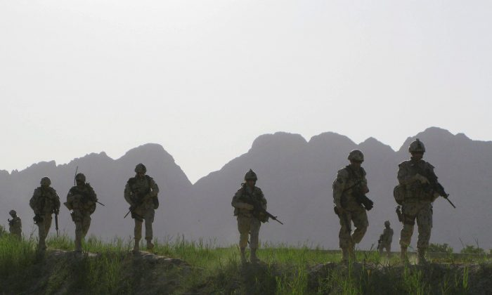 Canadian soldiers patrol an area in the Dand district of southern Afghanistan on June 7, 2009. The government is drafting a letter of assurance it hopes will end a class-action lawsuit by Afghan veterans related to an overhaul of their benefits and entitlements initiated 10 years ago. (The Canadian Press/Colin Perkel)