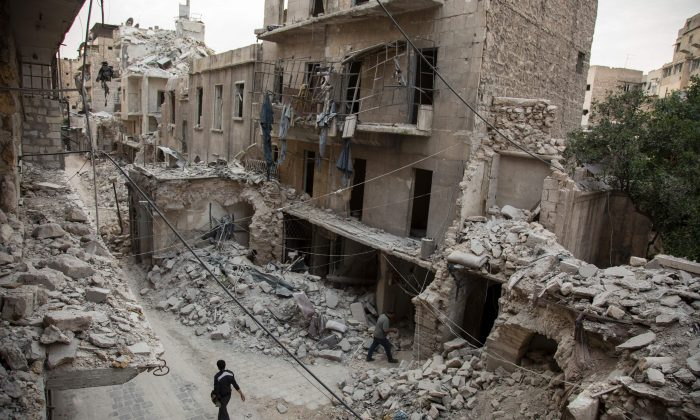 A Syrian man walks past destroyed buildings on May 2, 2016, in Aleppo's Bab al-Hadid neighborhood which was targeted recently by regime airstrikes. Aleppo residents ventured out onto the streets, taking advantage of a lull in violence in the northern Syrian city as the United States pushed to salvage a ceasefire. (Karam al-Masri/AFP/Getty Images)