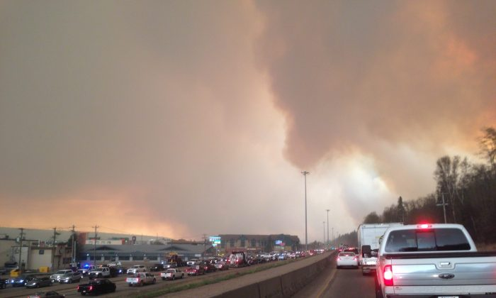 Smoke from a wildfire rises in the air as cars line up on a road in Fort McMurray, Alberta, Tuesday, May 3, 2016. At least half of a northern Alberta city was ordered evacuated Tuesday as a wildfire whipped by winds engulfed homes and sent ash raining down on residents. (Greg Halinda/The Canadian Press via AP) MANDATORY CREDIT