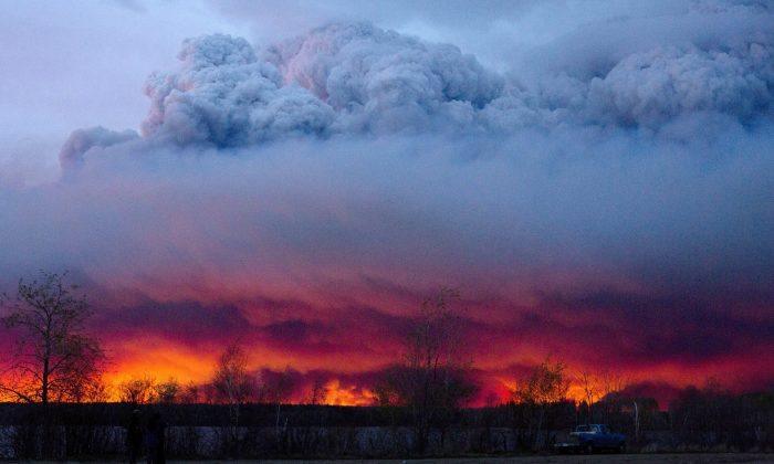 A wildfire moves towards the town of Anzac from Fort McMurray, Alberta, on May 4, 2016. Alberta declared a state of emergency Wednesday as crews frantically held back wind-whipped wildfires. Unseasonably hot temperatures combined with dry conditions have transformed the boreal forest in much of Alberta into a tinder box. (Jason Franson/The Canadian Press via AP) MANDATORY CREDIT