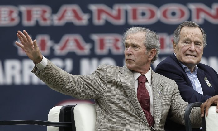 Former Presidents George W. Bush (L) and George H.W. Bush wave before a game between the Oakland Raiders and Houston Texans at Reliant Stadium on November 17, 2013 in Houston, Texas.  (Photo by Bob Levey/Getty Images)
