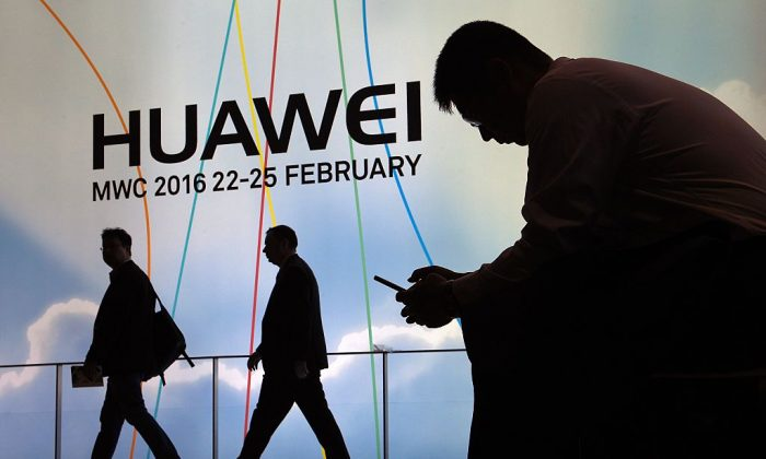 A man uses a mobile phone next to the stand of Chinese telecommunications company Huawei in Barcelona, on Feb. 22, 2016. The company has been widely accused of being a threat to national security. (Lluis Gene/AFP/Getty Images)