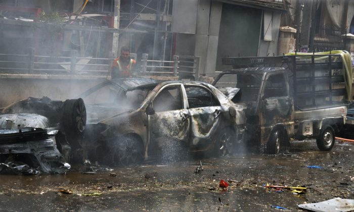"""In this photo released by the Syrian official news agency SANA, a firefighter tries to extinguish a fire at the scene where one of the rockets hit the Dubeet hospital in the central neighborhood of Muhafaza in Aleppo, Syria, Tuesday, May 3, 2016. Shells and mortar rounds are raining down on every neighborhood Aleppo,"""" said Aleppo-based health official Mohammad Hazouri, speaking from Al-Razi hospital. (SANA via AP)"""