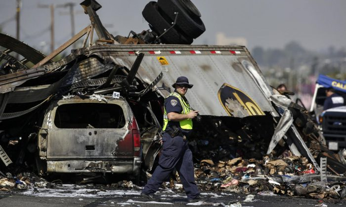 A California Highway Patrol investigator takes photographs at the scene of a multi-vehicle crash caused by drag racing on the 5 Freeway in Commerce that killed three people. (Irfan Khan/The Los Angeles Times)