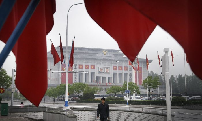 A North Korean man walks out of an underpass while seen framed by the Workers' Party flags, in front of the April 25 House of Culture, the venue for the 7th Congress of the Workers' Party of Korea on Friday, May 6, 2016, in Pyongyang, North Korea.  (AP Photo/Wong Maye-E)