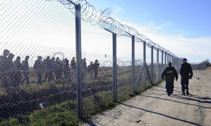 FILE - In this Feb. 22, 2016 file photo patrolling Hungarian police officers watch migrants behind a temporary protective fence at the border between Hungary and Serbia near Morahalom, 179 kms southeast of Budapest, Hungary. Thousands of migrants have continued to travel through Hungary on their way toward western Europe, despite fences, border closures and the European Union's deal with Turkey to stop sea crossings to Greece. (Zoltan Gergely Kelemen/MTI via AP, file)