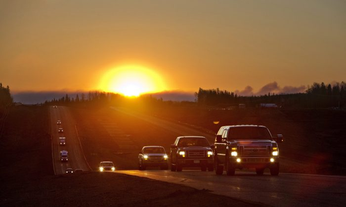 Evacuees leave Fort McMurray in the early morning, after being stranded north of wildfire in Fort McMurray, Alberta, Canada on Friday, May 6, 2016. (Jason Franson/The Canadian Press via AP)