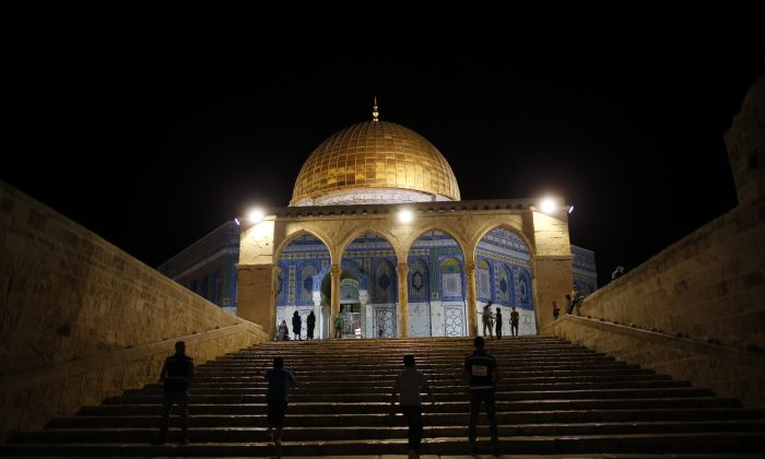 """Palestinian walk past the Dome of the Rock in the al-Aqsa Mosque compound in Jerusalem during """"tarawih"""" prayer marking the first evening of Islam's holy month of Ramadan, on June 6, 2016. (Ahmad Gharabli/AFP/Getty Images)"""