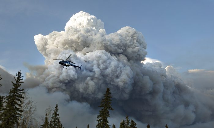 A helicopter flies past a wildfire in Fort McMurray, Alberta on Wednesday, May 4, 2016. Alberta declared a state of emergency Wednesday as crews frantically held back wind-whipped wildfires that have already torched homes and other buildings in Canada's main oil sands city of Fort McMurray, forcing thousands of residents to flee. (Jason Franson /The Canadian Press via AP) MANDATORY CREDIT