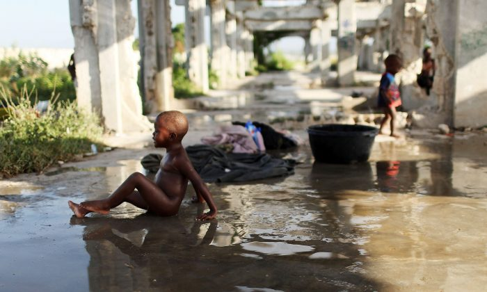 A boy bathes in a camp for individuals who have lost their homes in the Jan. 12, 2010 earthquake, in Cite Soleil, a historically impoverished area of Port-au-Prince, Haiti, on Oct. 31, 2010. (Spencer Platt/Getty Images)