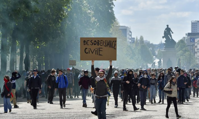"""A young man holds a placard reading """"Civil Disobedience"""" as demonstrators take part in a protest against the French government's proposed labor reforms, in Nantes, western France, on April 28, 2016. Protests turned violent in Paris and other French cities today as tens of thousands of workers and students made a new push for the withdrawal of a hotly contested labor bill. (Loic Venance/AFP/Getty Images)"""