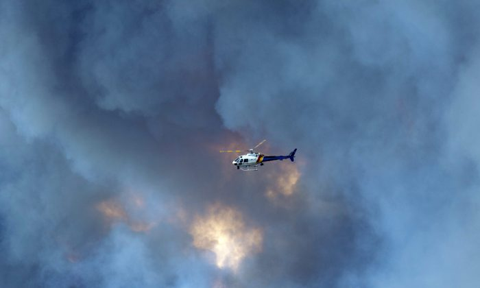 A RCMP helicopter flies past smoke from a wildfire about 18 miles south of Fort McMurray, Alberta, along highway 63, on May 6, 2016. (Jonathan Hayward/The Canadian Press via AP)