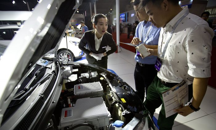 Visitors examine a JAC iEV5 electric car at the Beijing International Auto Exhibit April 25. The surge of electric vehicles will increase demand for lithium, a vital raw material in the production of lithium ion batteries. (AP Photo/Mark Schiefelbein)