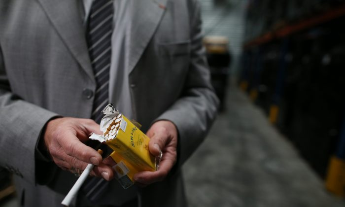 A French customs officer holds a pack of cigarettes, part of the 14 million seized by the French customs in Le Havre harbor on Oct. 9, 2015. (Charly Triballeau/AFP/Getty Images)