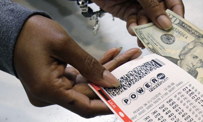 A clerk hands over a Powerball ticket for cash at Tower City Lottery Stop in Cleveland on Jan. 13, 2016. (AP Photo/Tony Dejak)