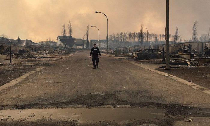 In this May 5, 2016, photo provided by the Royal Canadian Mounted Police Alberta, an RCMP officer surveys the damage on a street in fire-ravaged Fort McMurray, Alberta. More than 80,000 people have left Fort McMurray, in the heart of Canada's oil sands as a wildfire that has devastated the area exploded in size.  (Royal Canadian Mounted Police Alberta via The Canadian Press via AP)