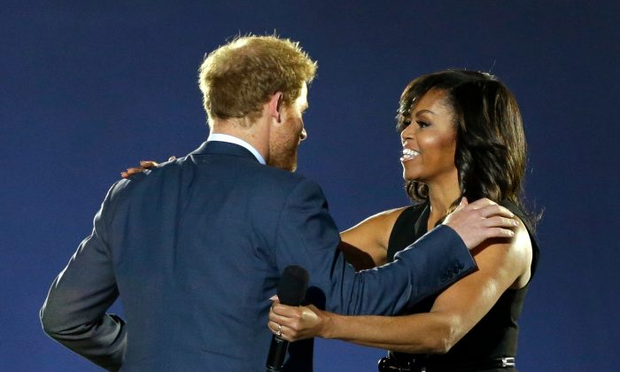 Britain's Prince Harry, left, greets first lady Michelle Obama on stage during the opening ceremony for the Invictus Games, Sunday, May 8, 2016, in Kissimmee, Fla. (AP Photo/John Raoux)