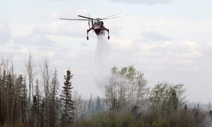 A helicopter drops water on hot spots along a highway to Fort McMurray, Canada, Sunday, May 8, 2016. (Ryan Remiorz/The Canadian Press via AP)