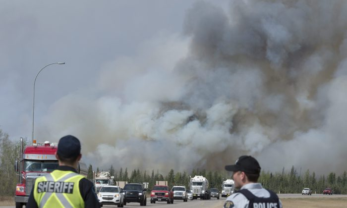 Police watch a convoy of cars and trucks pass a wildfire as they are evacuated from Fort McMurray, Alberta, on  May 7, 2016. Federal scientists are predicting the 2020 summer wildfire season could be well above average for much of Canada, especially Western provinces. 