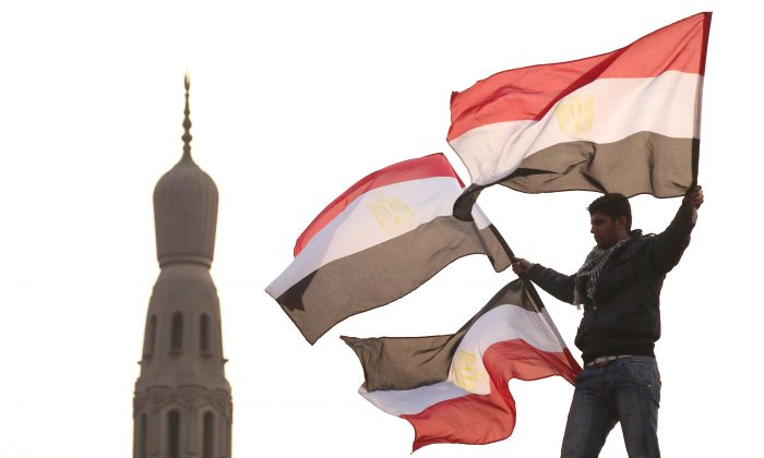 A youth waves Egyptian flags from a lamp post in Tahrir Square in Cairo, Egypt, on Feb. 1, 2011. (Peter Macdiarmid/Getty Images)