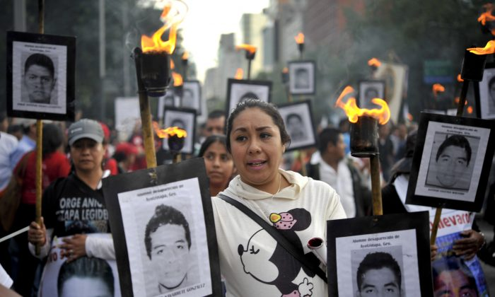 The parents of 43 missing students from the Ayotzinapa Teachers' College hold their portraits and torches during a march 18 months after their disappearance in Mexico City, Mexico, on April 26, 2016. (Yuri Cortez/AFP/Getty Images)