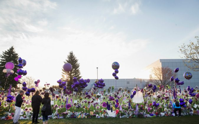 Music fans visit a memorial created outside Paisley Park, the home and studio of Prince, on April 23, 2016, in Chanhassen, Minnesota. Prince, 57, was pronounced dead shortly after being found unresponsive in an elevator April 21 at Paisley Park. (Scott Olson/Getty Images)