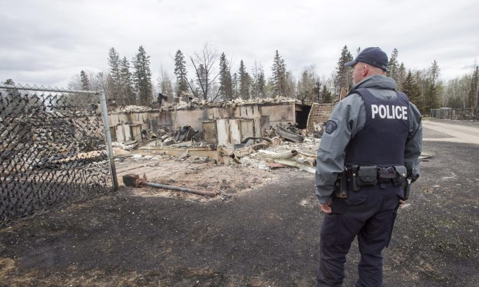 A police officer looks at the wildfire destruction in the Abasand neighbourhood of Fort McMurray on May 9, 2016. (The Canadian Press/Ryan Remiorz)