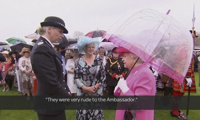 """In image made from pool video, Queen Elizabeth II speaks with Metropolitan Police Commander Lucy D'Orsi in the garden of Buckingham Palace in London, Tuesday, May 10, 2016. Queen Elizabeth II has been overheard on video describing Chinese officials as """"very rude to the ambassador"""" in a conversation with a senior police officer at a Buckingham Palace event celebrating her birthday. Subtitles as appears on source video. (Image from Pool Video via AP Video)"""