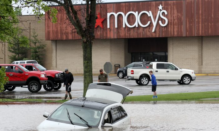 Cole Lyons, from left, Austin Reel and Cameron Reel look at a submerged car in the parking lot of Town Square Mall, Tuesday, May 10, 2016, in Owensboro, Ky., after heavy rains swept through Daviess County and flooded the lot. (Greg Eans/The Messenger-Inquirer via AP) MANDATORY CREDIT