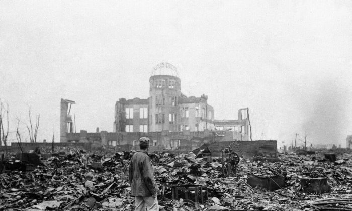 In this Sept. 8, 1945, file photo, an allied correspondent stands in the rubble in front of the shell of a building that once was a movie theater in Hiroshima, Japan, a month after the first atomic bomb ever used in warfare was dropped by the U.S. on Monday, Aug. 6, 1945. (AP Photo/Stanley Troutman, File)