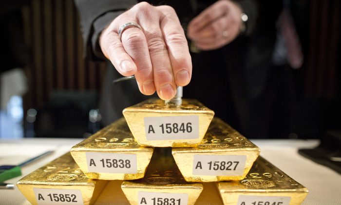 An employee of the German Federal Bank checks the core of a bar of gold during a press conference at the German Federal Bank in Frankfurt am Main, western Germany, on January 16, 2013. (FRANK RUMPENHORST/AFP/Getty Images)