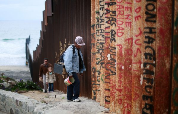 A man walks along the U.S.-Mexico border wall in Tijuana, Mexico, on Feb. 22, 2015. (Sandy Huffaker/Getty Images)