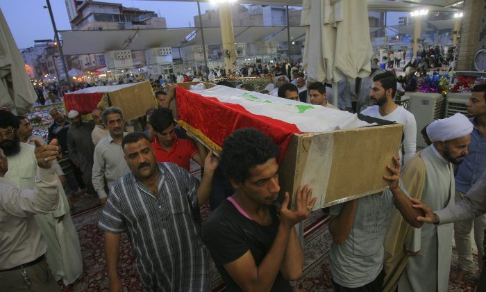Mourners carry the Iraqi flag-draped coffins of bomb victims, Murtada Mohammed, 26, and his brother Sadiq Mohammed, 22, during their funeral procession at the holy shrine of Imam Ali in Najaf, 100 miles (160 kilometers) south of Baghdad, Iraq, Wednesday, May 11, 2016. An explosives-laden car bomb ripped through a commercial area in a predominantly Shiite neighborhood of Baghdad on Wednesday, killing and wounding dozens of civilians, a police official said. (AP Photo/Anmar Khalil)